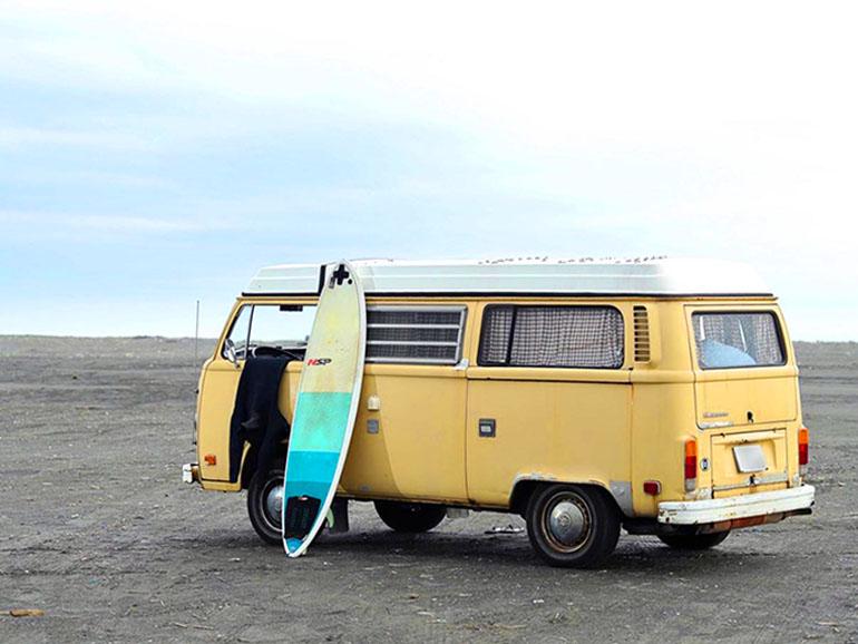 砂浜に取れられたキャンピングカーとサーフボード
