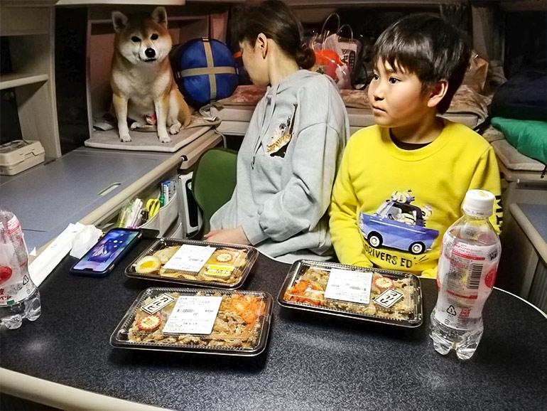 車内でお弁当を食べる家族
