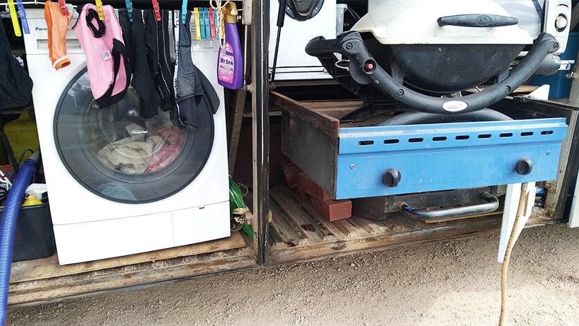 外部収納庫に積まれた洗濯機やコンロ