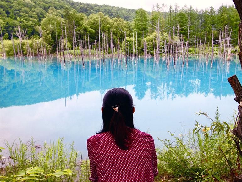 美瑛の青い池を眺める女性