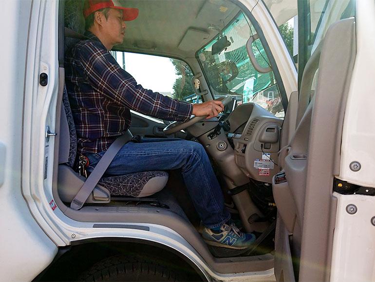 ライトキャブコンの運転席に座る男性