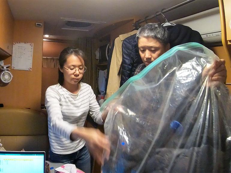 布団を圧縮袋に入れている夫婦