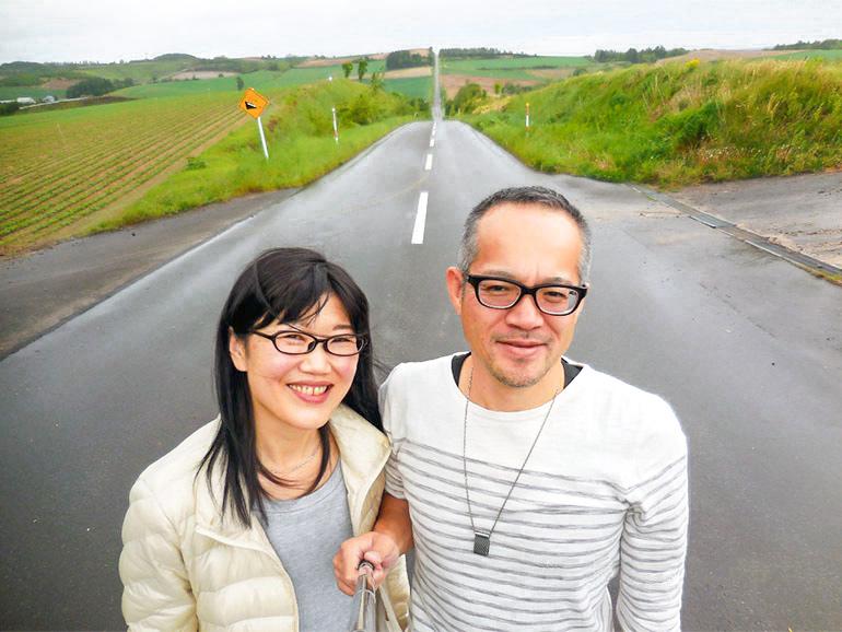 北海道の絶景ロード「ジェットコースターの路」で記念撮影するささきご夫婦