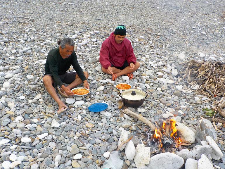 アルマイト鍋で焚き火調理をする男性