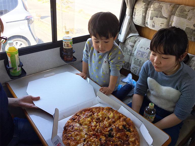 キャンピングカーの車内でピザを食べる家族