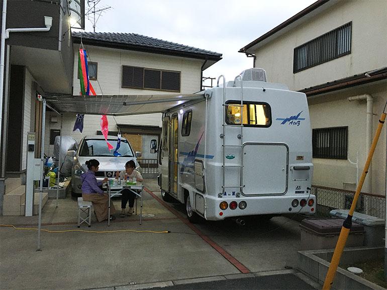 家の前に停められたキャンピングカーの横でBBQをする家族