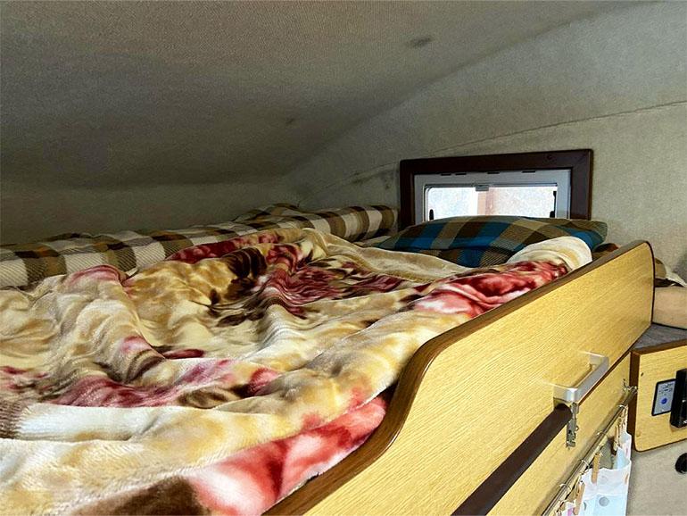 寝具が敷かれたキャンピングカーのバンクベッド