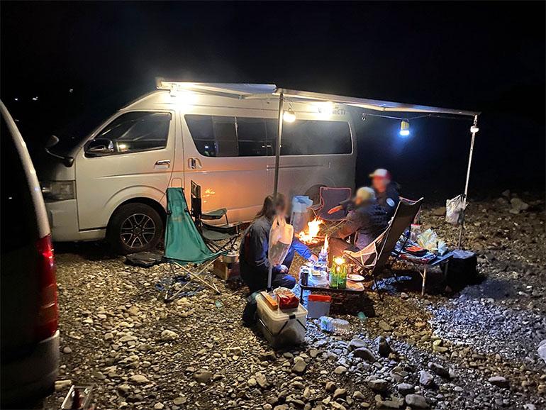 サイドオーニングを広げてキャンプをしている風景