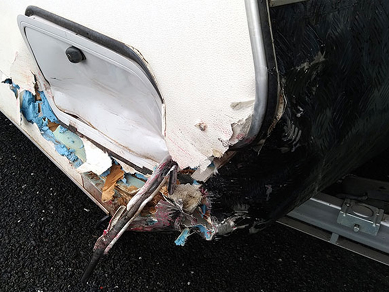 事故で側面がひしゃげたキャンピングトレーラー