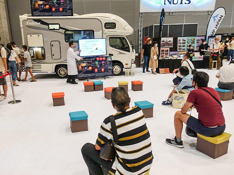 ナッツRVの展示ブースにて充電システム「エボリューション」を紹介している様子