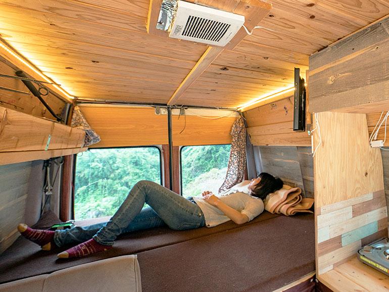 キャンピングカー  ベッドで寝転ぶ女性