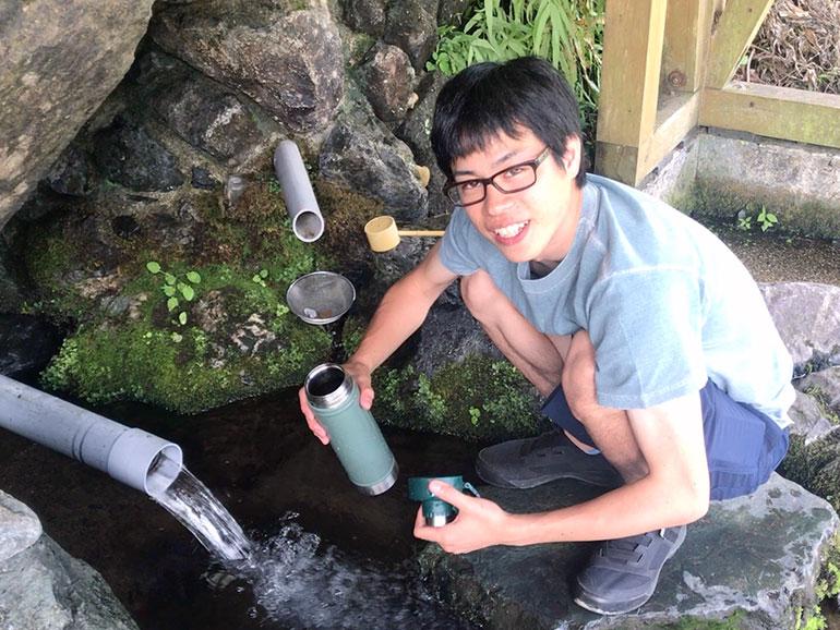 湧き水を汲む男性