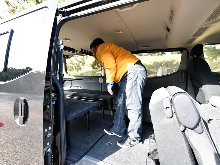 日産キャラバンマルチベッドの車内で立つ男性