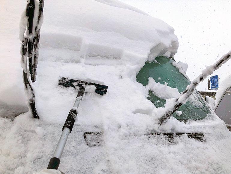 バンに降り積もった雪を降ろしている様子