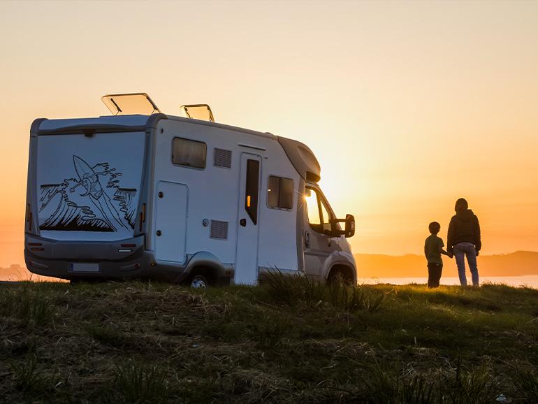 キャンピングカーの横で夕日を見る親子