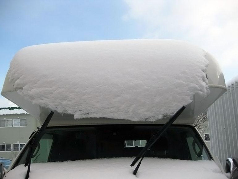 屋根に雪の積もったキャンピングカー
