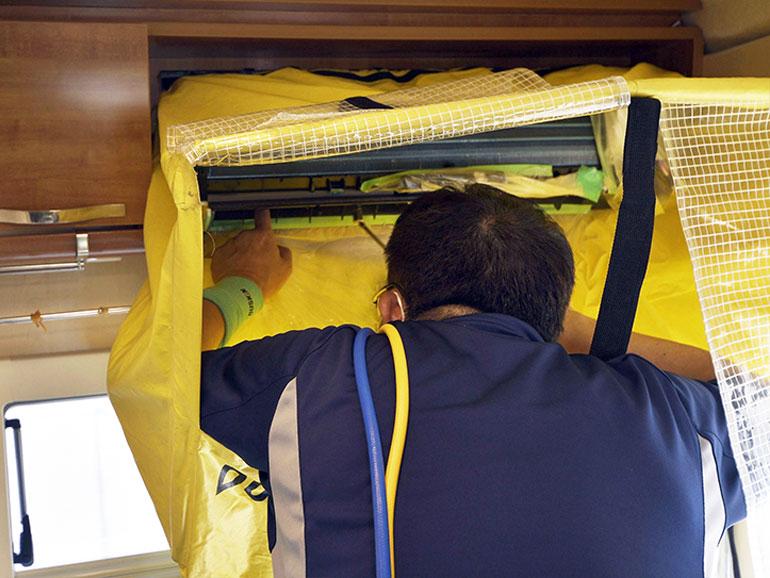 エアコン内部を洗浄剤噴霧器で洗浄している様子