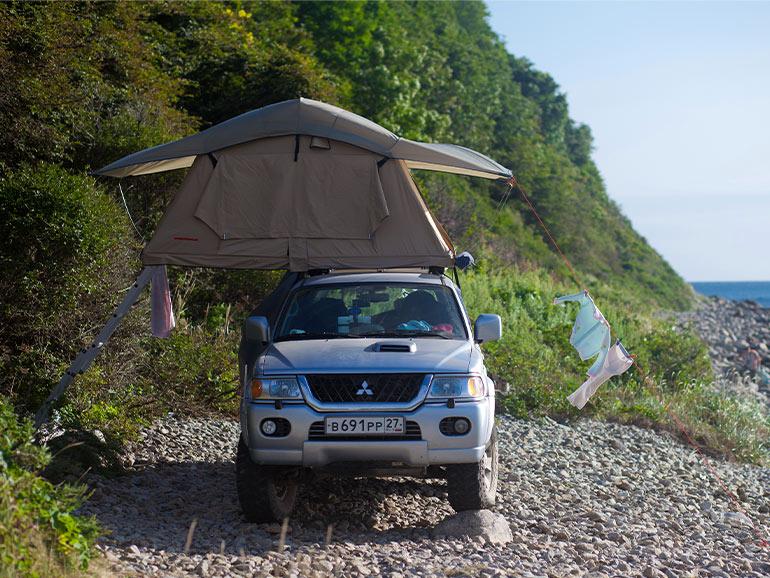 海沿で停車したルーフトップテントを積んだ乗用車
