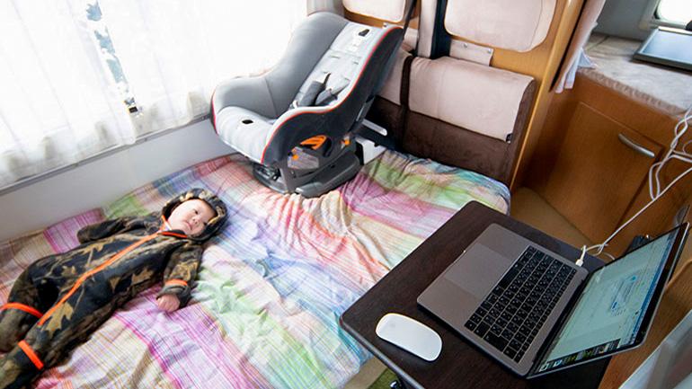 キャンピングカーの車内で寝そべる赤ちゃん