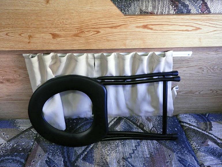 椅子型折りたたみ式簡易トイレを畳んでいるところ