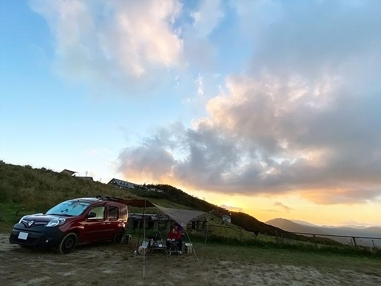 夕日が沈む中オートキャンプをしている風景