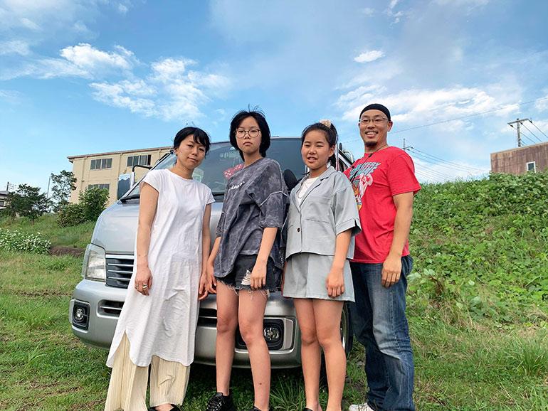 DIYした車中泊仕様車の前で並ぶ家族